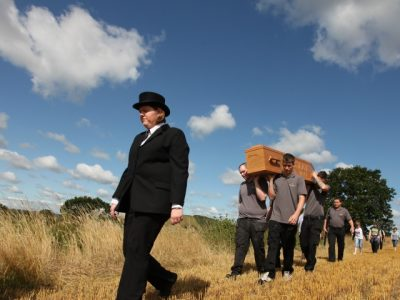woman leading coffin being carried across field